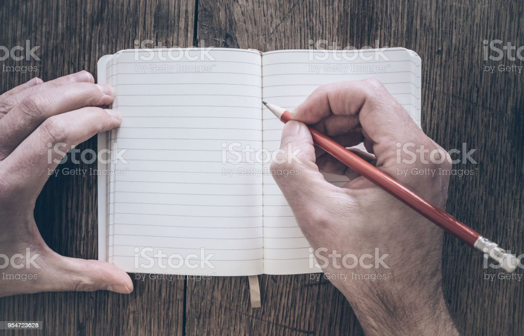 Draufsicht der Mann mit Bleistift schreiben auf Notizblock auf Schreibtisch aus Holz - Lizenzfrei Altertümlich Stock-Foto