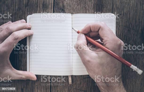 Draufsicht Der Mann Mit Bleistift Schreiben Auf Notizblock Auf Schreibtisch Aus Holz Stockfoto und mehr Bilder von Schreiben