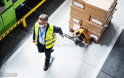 Top view of man worker or technician with protective mask working in industrial factory or warehouse.