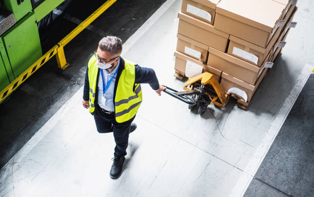 Top view of man worker with protective mask working in industrial factory or warehouse. Top view of man worker or technician with protective mask working in industrial factory or warehouse. only mature men stock pictures, royalty-free photos & images