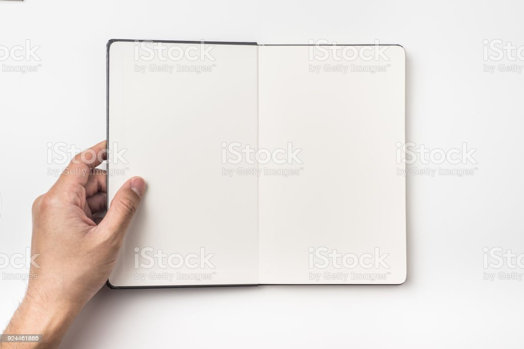Top view of man's hand hold black hardcover notebook