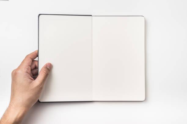 draufsicht des mannes hand halten schwarzen hardcover notizbuch - zeitschrift aufgeschlagen stock-fotos und bilder