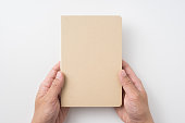 Top view of man's hand holding hardcover kraft notebook