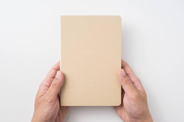 draufsicht des mannes hand, die gebundene kraft notebook - zeitschrift aufgeschlagen stock-fotos und bilder