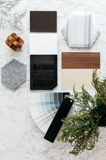 bovenaanzicht van materiaal selecties met inbegrip van graniettegels, marmer tegels, akoestische tegels, walnoot en ash hout laminaat en geschilderde kleurstaal met planten en bloemen op marmeren bovenste tafel. - kleurenwaaier stockfoto's en -beelden