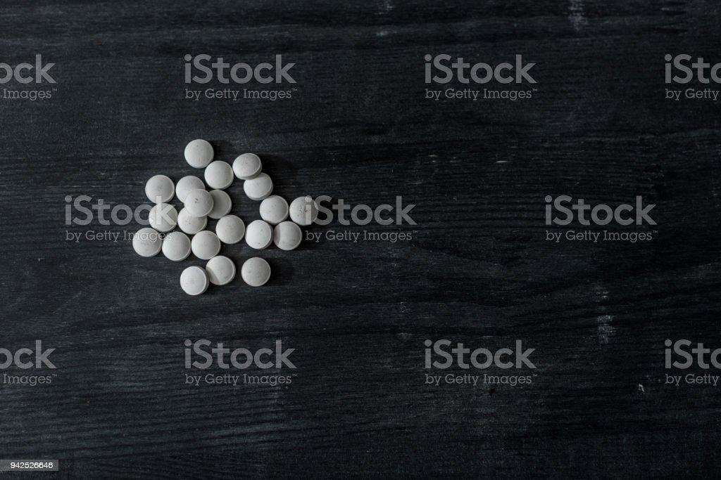 vista superior de las píldoras de mdma en la superficie de madera negra - foto de stock