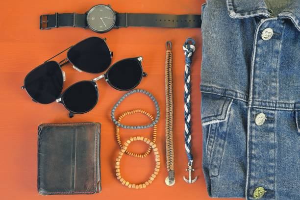 Top view of men accessories. Hipster or modern man concept. Accessories for going for a walk. Male fashion accessories, flat lay on coral pink background. Wallet, bracelets, sunglasses - shades, watch, denim jacket stock photo