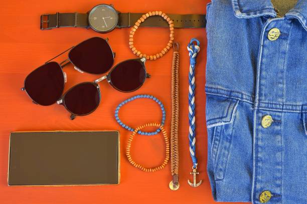 Top view of men accessories. Hipster or modern man concept. Accessories for going for a walk. Male fashion accessories, flat lay on coral pink background. Wallet, bracelets, sunglasses - shades, watch, denim jacket and mobile phone stock photo
