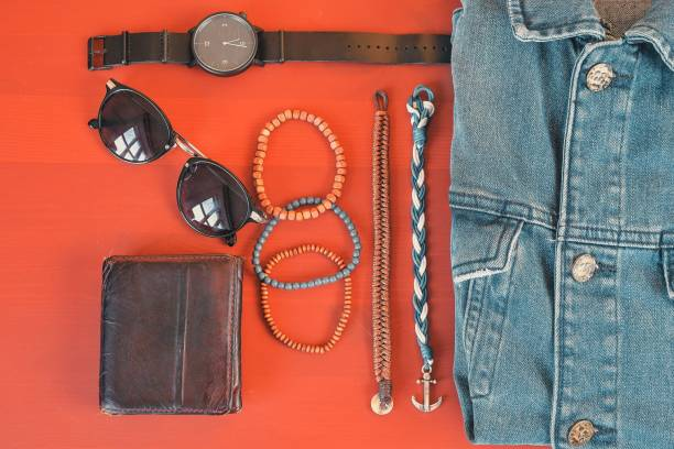 Top view of men accessories. Hipster or modern man concept. Accessories for going for a walk. Male fashion accessories, flat lay on coral pink background stock photo