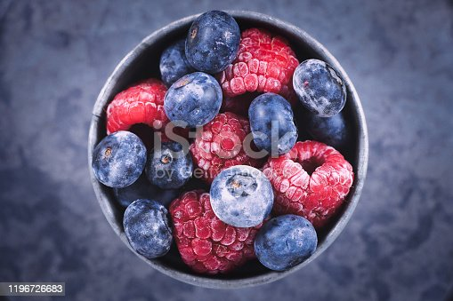 istock Top view of mixed blueberry and raspberry fruits in iron cup 1196726683