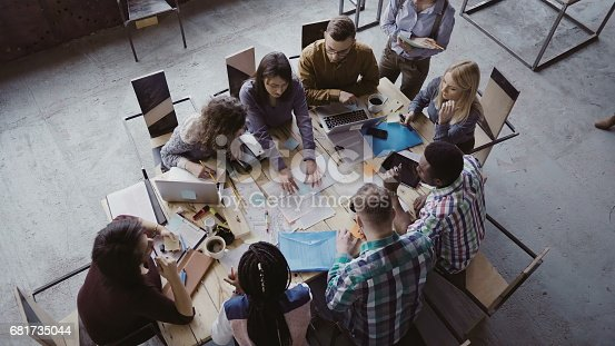 681735120istockphoto Top view of mixed race business team sitting at the table at loft office and working. Woman manager brings the document 681735044