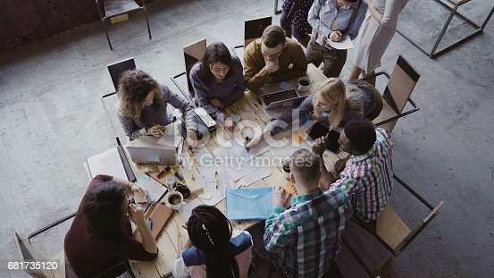 istock Top view of mixed race business team sitting at the table at loft office and working. Woman manager brings the document 681735120