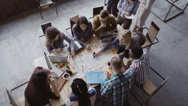widok z góry mieszanego zespołu biznesowego wyścigu siedzi przy stole w biurze na poddaszu i pracy. kobieta kierownik przynosi dokument - białoruś zdjęcia i obrazy z banku zdjęć