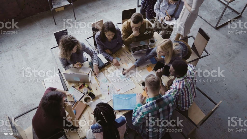 Top view of mixed race business team sitting at the table at loft office and working. Woman manager brings the document - foto stock