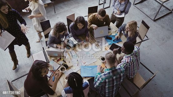 681735120istockphoto Top view of mixed race business team sitting at the table at loft office and working. Woman manager brings the document 681735190