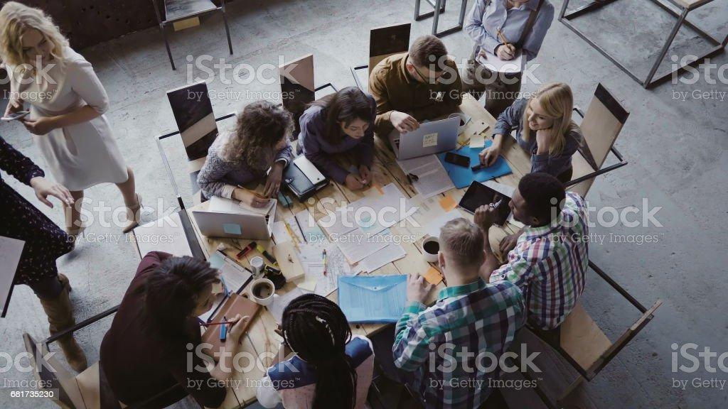 Vista superior del equipo de raza mixta de negocios sentado en la mesa en la oficina de loft y trabajo. Gestor de la mujer que trae el documento - foto de stock
