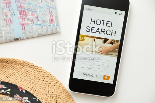 istock Top view of mobile phone, hotel search on the screen 617381244