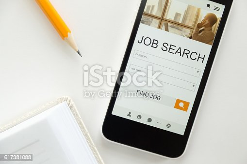 istock Top view of mobile phone lying on desk, job search 617381088