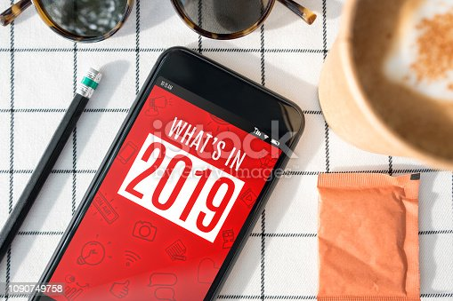 istock Top view of mobile phone with what is in 2019 with coffee cup,sunglasses,pencil on white table cloth.digital influencer blogger lifestyle 1090749758