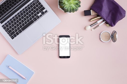Top view of mockup of mobile phone with white blank copy space screen in female hand. Flat lay women workspace with laptop, decorative cosmetic set, stationery, succulent flower