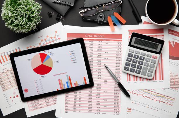 Top-Ansicht des modernen schwarzen Bürotischs mit Tablet-PC und Finanzberichten, Notebook, Bleistift und vieles. Flaches Laientabellenlayout. – Foto