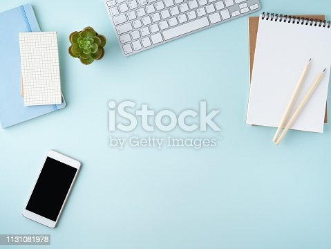 istock Top view of modern blue office desktop with blank notepad, computer, smartphone. Mock up, empty space 1131081978