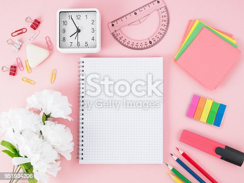 818533812 istock photo Top view of modern bright pink office desktop with notebook in a cage, flowers, school supplies on table, empty space for text. Back to school concept. 951934206