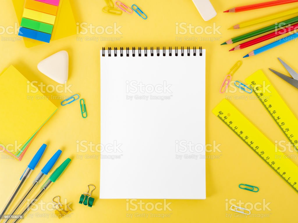 Top View Of Modern Bright Yellow Office Desktop With Blank Notepad, School  Supplies On Table