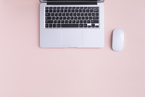 Top view of modern laptop isolated on pink background.