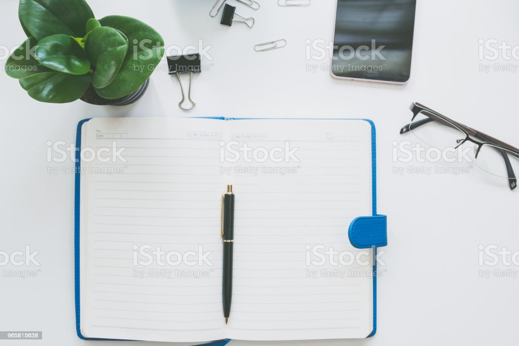 Top view of modern work space office desk Top view of modern work space office desk table with notebook page , smart phone and copy space Blank Stock Photo