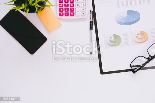 istock Top view of modern work space office desk table with smart phone , pen ,report for financial and copy space 975440210