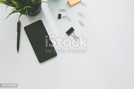 istock Top view of modern work space office desk table with smart phone , pen and copy space 975440332