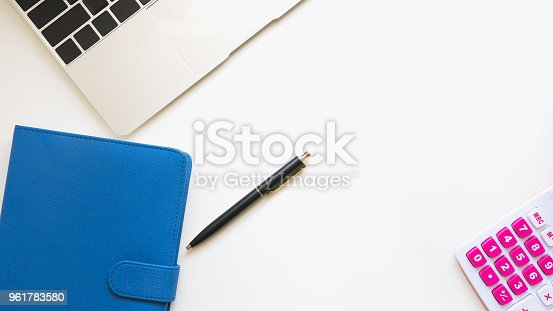 istock Top view of modern workspace office desk table with blue note book ,calculator ,pen and tablet 961783580