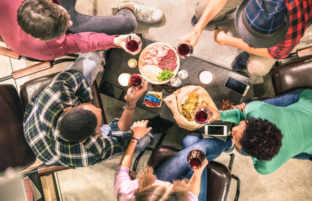 top view of multi racial friends tasting red wine and having fun at fashion bar winery restaurant - multicultural friendship concept with people enjoying time drinking together - indoor neutral filter - eating technology stock photos and pictures