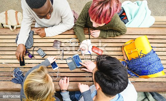 istock Top view of multiracial friends using mobile smart phone - Addiction concept with young people on new tech devices - Multicultural students having fun on social media networking - Warm vivid filter 858705256