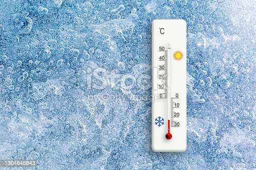 Top view of natural ice texture with celsius scale thermometer. Ambient temperature minus 23 degrees