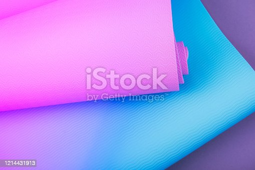 637596492 istock photo Top view of neon colored blue pink yoga mat on violet background.  Space for  text. 1214431913