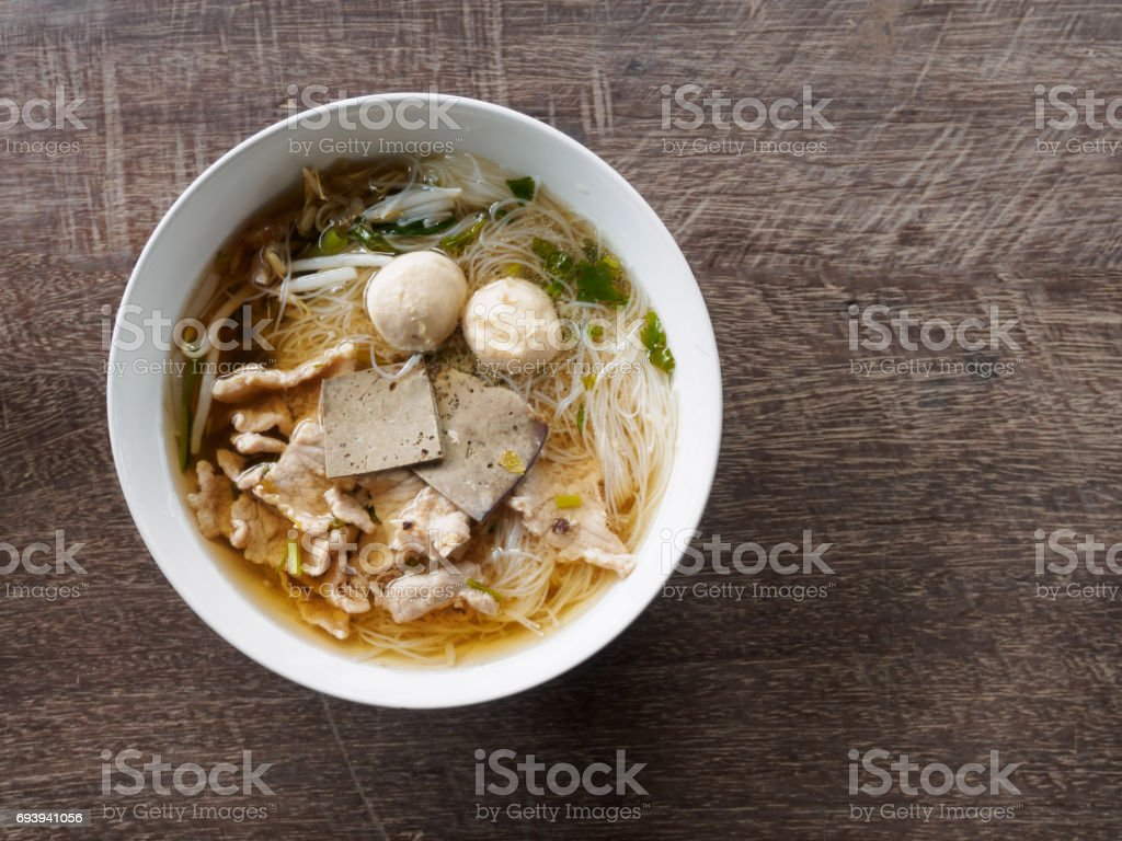 Top view of noodle pork in bowl on wooden table stock photo