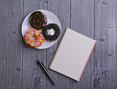istock Top view of Notebook, ballpen, and doughnut on wooden background 1292836037