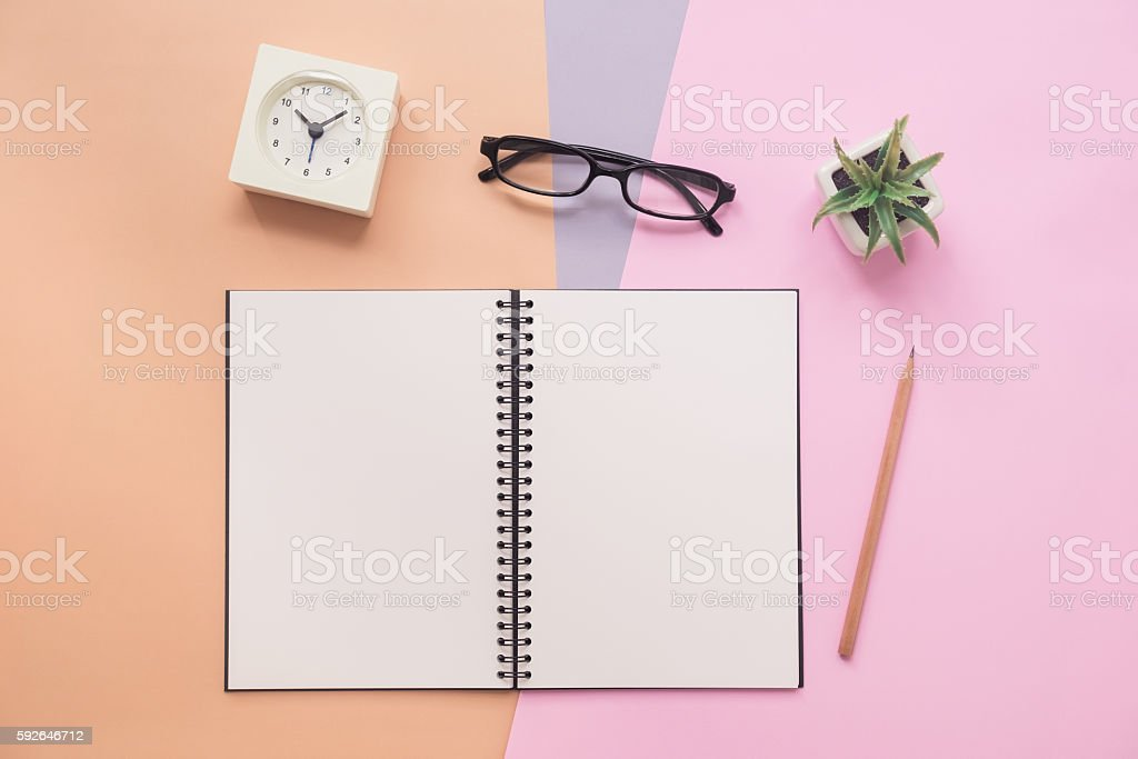 Top view of notebook with pen, eyeglasses, clock, plant