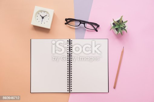 istock Top view of notebook with pen, eyeglasses, clock, plant 592646712