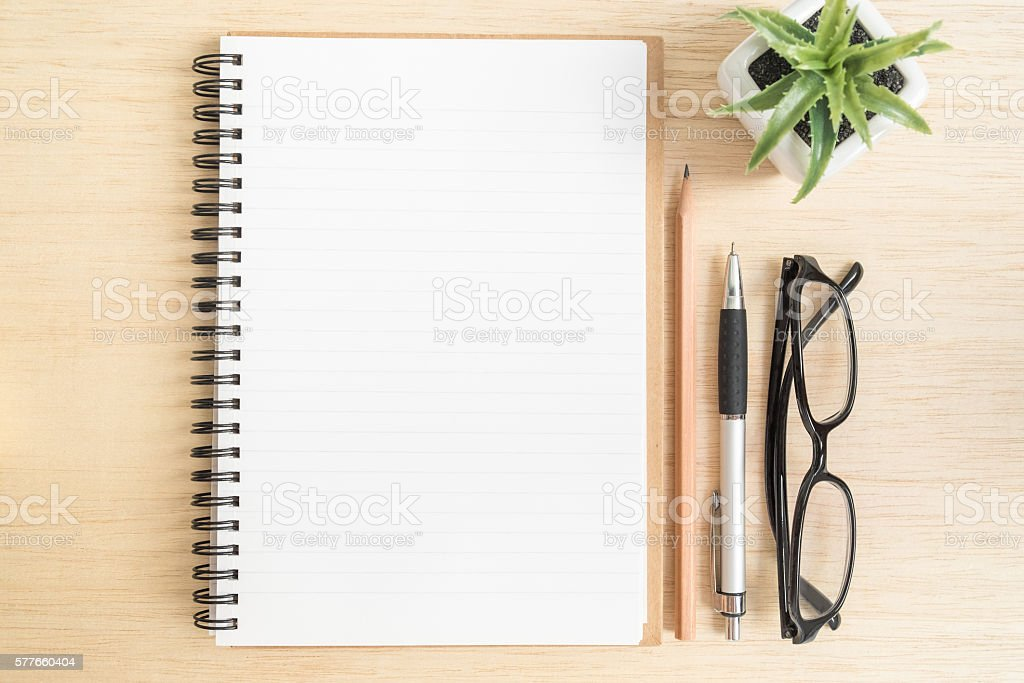 Top view of notebook with pencil, pen, eye glasses stock photo