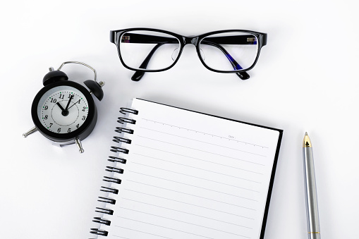 istock Top view of notepad, eyeglasses, pen and alarm clock 814596196