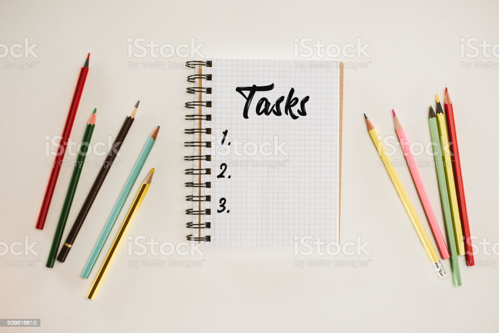 top view of notepad with blank tasks list lettering and colorful pencils isolated on white stock photo