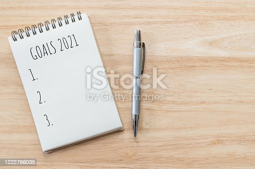 Top view of notepad with Goals List on wooden table, goals concept.