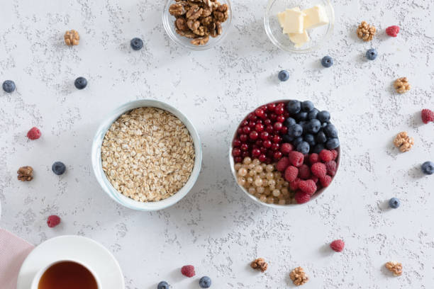 Top view of oat flakes in plate with berries, nuts, butter and cup of tea on textural white table, flat lay. stock photo