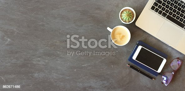 862672018 istock photo Top view of office desk on dark textured background 862671486