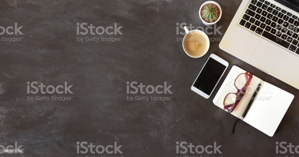 Top view of office desk on dark textured background stock photo