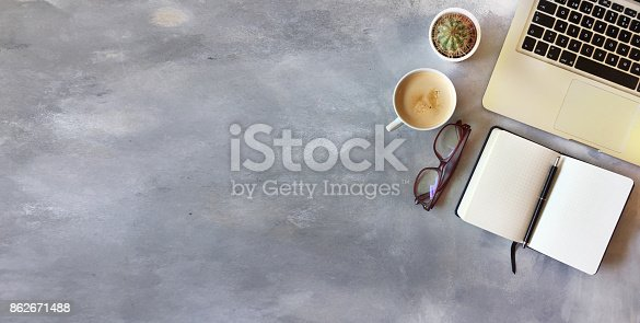 istock Top view of office desk on gray textured background 862671488