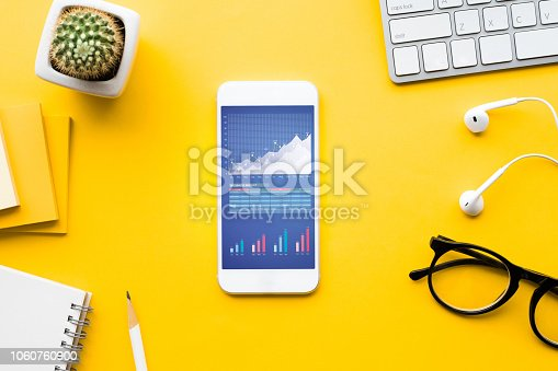 615494694 istock photo Top view of office desk table with graph chart on mock up smartphone 1060760900